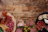Photo top view of cutting boards with delicious prosciutto, salami, bread, olives, breadsticks, and herbs on wooden table  with scattered spices