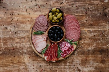 Top view of round cutting board with olives and sliced salami, prosciutto and ham on wooden table with scattered spices stock vector