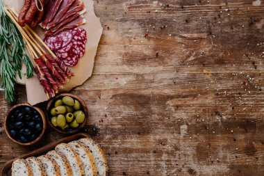 top view of cutting boards with delicious prosciutto, salami, bread, olives and herbs on wooden table  with scattered spices