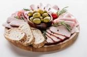 kulaté prkénko s lahodnou salám, šunka, olivy v misce, chléb a byliny na bílém stole