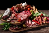 Schneidebretter mit köstlichen Salami, geräucherten Würstchen, Schinken und Gemüse auf einem rustikalen Holztisch