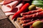 zblízka pohled na dřevěné krájecí desky s chilli, olivy, lahodnou krájený salám a šunka