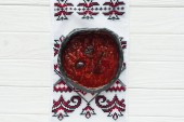 bowl of tasty traditional beetroot soup with embroidered towel on white wooden background