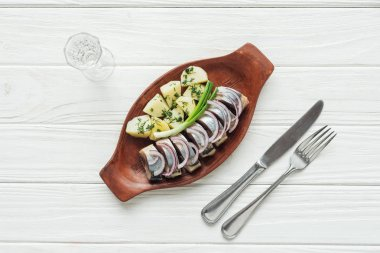 top view of marinated herring, potatoes and onions in earthenware plate with glass of vodka and cutlery on white wooden background