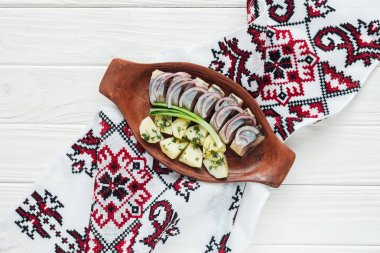 traditional marinated herring with potatoes and onions in earthenware plate with embroidered towel on white wooden background