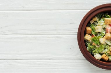 top view of traditional caesar salad with croutons in bowl on white wooden background with copy space