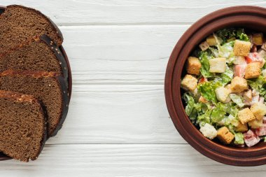 top view of delicious traditional caesar salad with croutons in bowl and rye bread on white wooden background
