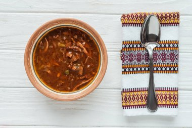 top view of delicious traditional mixed meat soup with spoon and embroidered towel on white wooden background