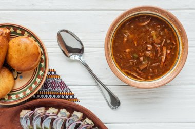 top view of tasty traditional mixed meat soup with mini pies and spoon on white wooden background