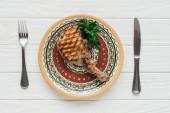 pohled shora na maso bifteky na desce s petrželkou a příbory na bílém pozadí dřevěná