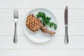 Fotografie pohled shora na chutné maso bifteky na desce s petrželkou a příbory na bílém pozadí dřevěná