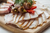 Fotografie close up of traditional sliced smoked lard with dill and chilli pepper on cutting board