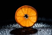 slice of fresh orange on black background with water drops