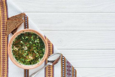traditional fish soup with green onion, embroidered towel, spoon and rye bread on white wooden background