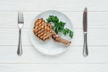 top view of tasty rib eye meat steak on plate with parsley and cutlery on white wooden background