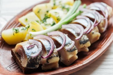 close up of tasty marinated herring with potatoes and onions in earthenware plate