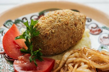 close up of chicken kiev with mashed potatoes, parsley, tomatoes and fried onions on plate with ornament