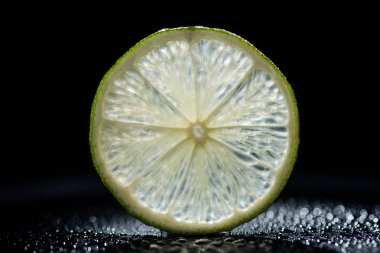 slice of fresh lime on black background