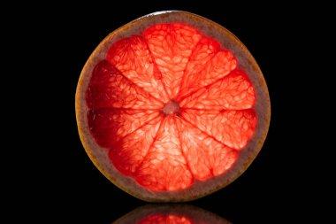 slice of fresh ripe grapefruit isolated on black