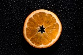 Photo slice of orange on black background with water drops