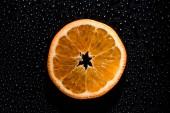 plátek pomeranče na černém pozadí s vodou kapky