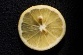 Fotografie plátek čerstvého citronu na černém pozadí s vodou kapky