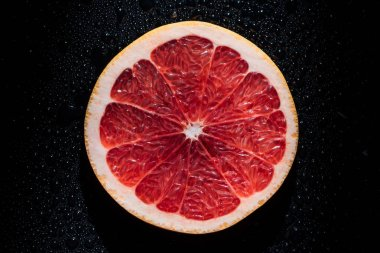 slice of grapefruit on black background with water drops