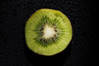 slice of fresh kiwi fruit on black background with water drops