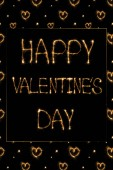 Fotografie close up view of happy valentines day light lettering and hearts on black background, st valentines day concept