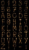 Fotografie close up view of light english alphabet and numbers on black background