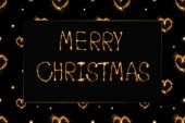 close up view of merry christmas light lettering and hearts light signs on black background