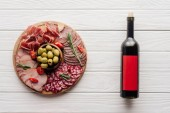 top view of bottle of red wine and assorted meat snacks on white wooden tabletop