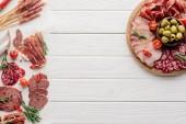 pohled shora uspořádání různé pochutiny z masa a olivy na bílé dřevěné pozadí