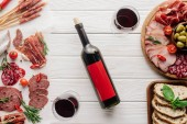 Fotografie složení potravin se láhev a sklenice červeného vína, kousky chleba, olivy a pochutiny z masa na bílé dřevěné stolní