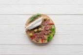 Draufsicht der Fleisch-Häppchen mit Oliven, Rosmarin und Basilikum Blätter auf weißen hölzernen Tischplatte