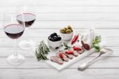 Fotografie zblízka pohled chutné maso předkrmy a sklenice červeného vína na bílém povrchu dřevěné