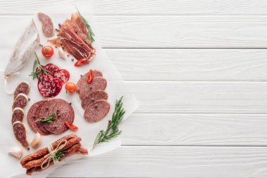 Top view of arrangement of various meat snacks and rosemary on white wooden backdrop stock vector