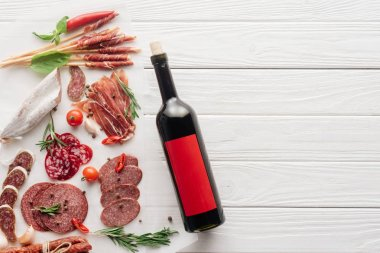 Top view of bottle of red wine and assorted meat snacks on white wooden tabletop stock vector