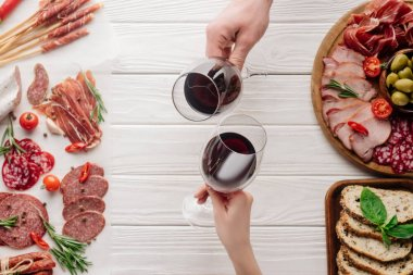 partial view of couple clinking glasses with red wine at white tabletop with meat appetizers