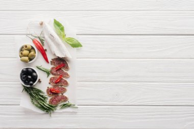 top view of meat appetizers with olives, rosemary and basil leaves on white wooden tabletop