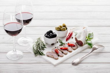 Close up view of tasty meat appetizers and glasses of red wine on white wooden surface stock vector
