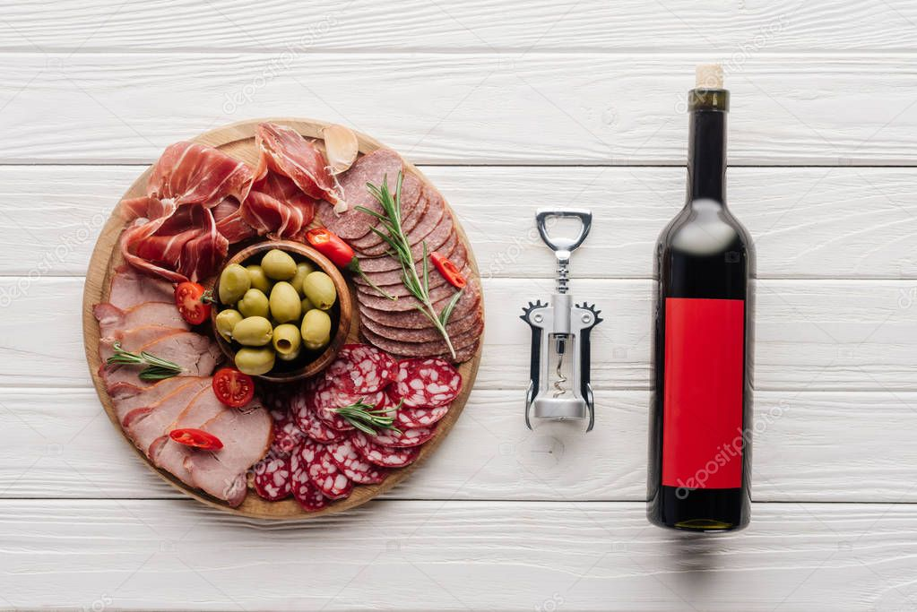 Flat lay with bottle of red wine, bottle opener and meat snacks on wooden surface stock vector