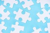 full frame of white puzzles arrangement on blue backdrop
