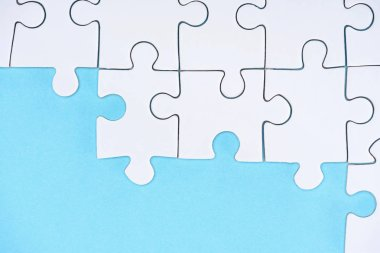 top view of white puzzles arrangement on blue background