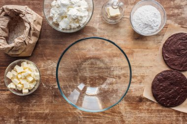 top view of empty glass bowl and ingredients for delicious homemade cake on wooden table
