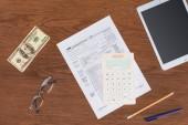 pohled shora daňové formuláře, Kalkulačka a dolar bankovky na dřevěný stůl na pracovišti