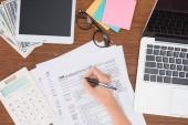 Blick auf Frau füllen Steuerformulare am Arbeitsplatz mit digitalen Geräten und Schreibwaren beschnitten