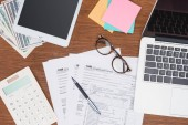 top view of tax forms, digital devices and stationery on desk