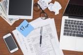 pohled shora daňových formulářů, digitálních zařízení a modrou kartu s april 17 Datum na stole
