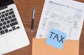 pohled shora daňové formuláře, laptop a modré karty s slovo daň na pracovišti